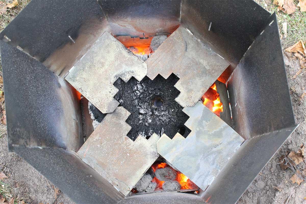 Elda upp stubbar Referensstubben nr 2 Gammal murken och fuktig stubbe med djupt liggande rötter i en stubbskorsten där briketter har tänts och stubben eldas upp.
