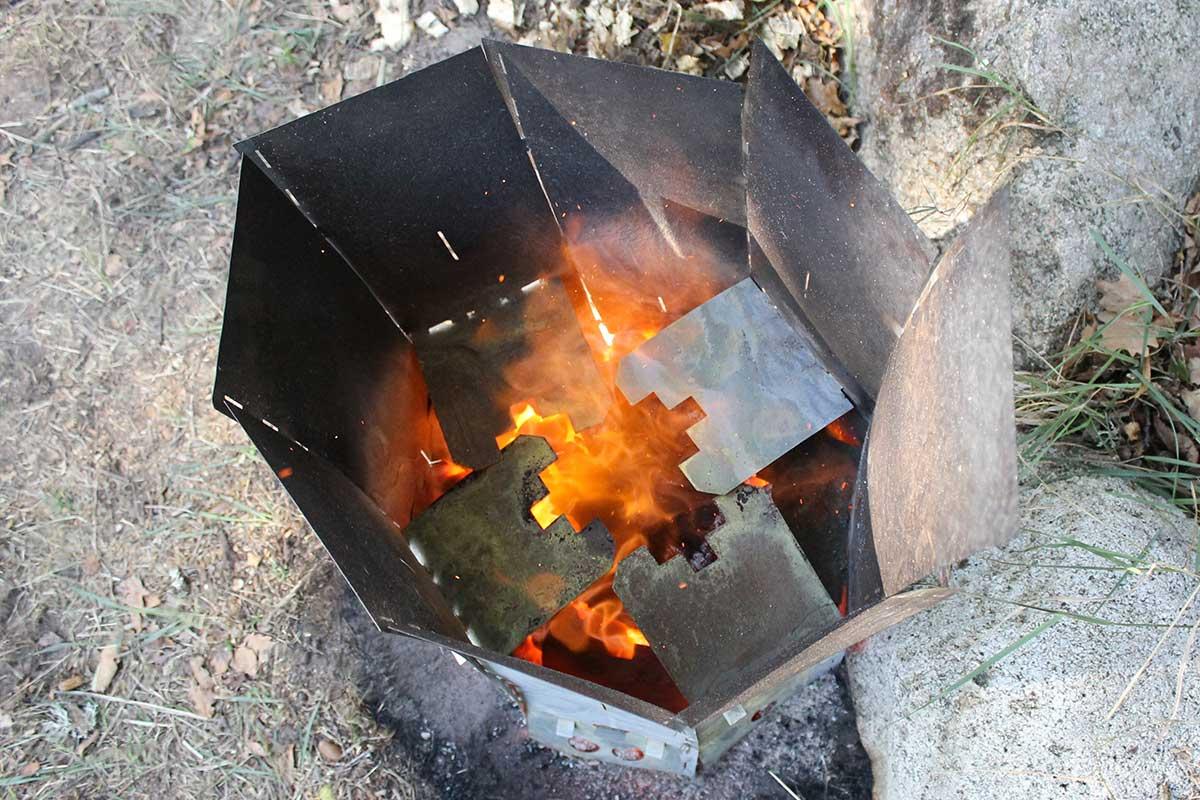 Elda upp stubbar Referensstubben nr 3 Stubbe vid stenmur i en stubbskorsten där briketter har tänts och stubben eldas upp.